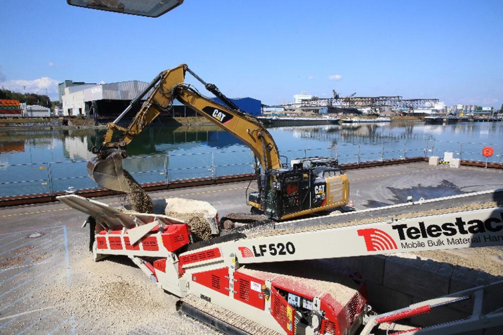 Per LKW angeliefertes sauberes Erdmaterial wird mittels Förderband auf dem Schiffsanleger ...