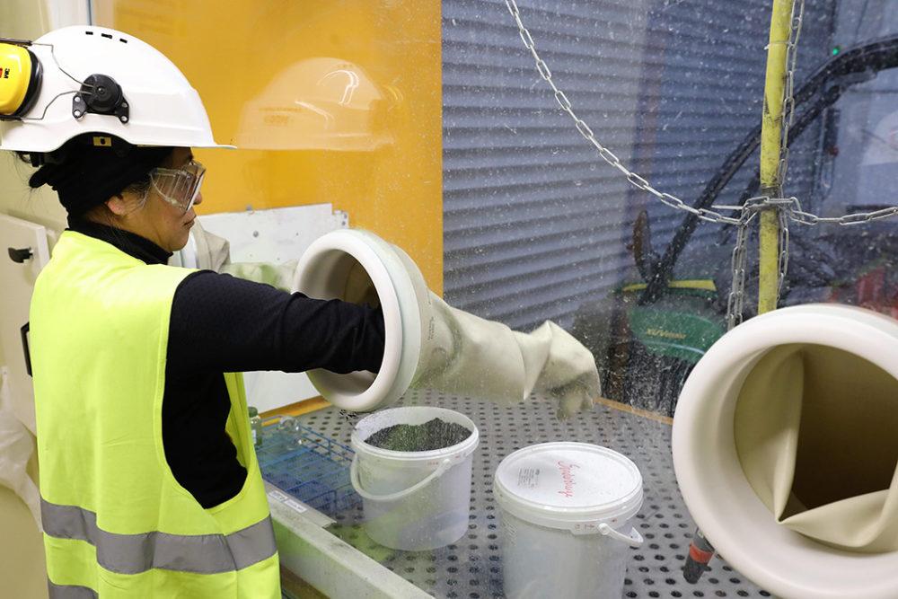 Eine Umweltnaturwissenschaftlerin bereitet im Schutze einer Glovebox das belastete Erdreich für die labortechnische Untersuchung vor. Quelle: Pressefoto Roche