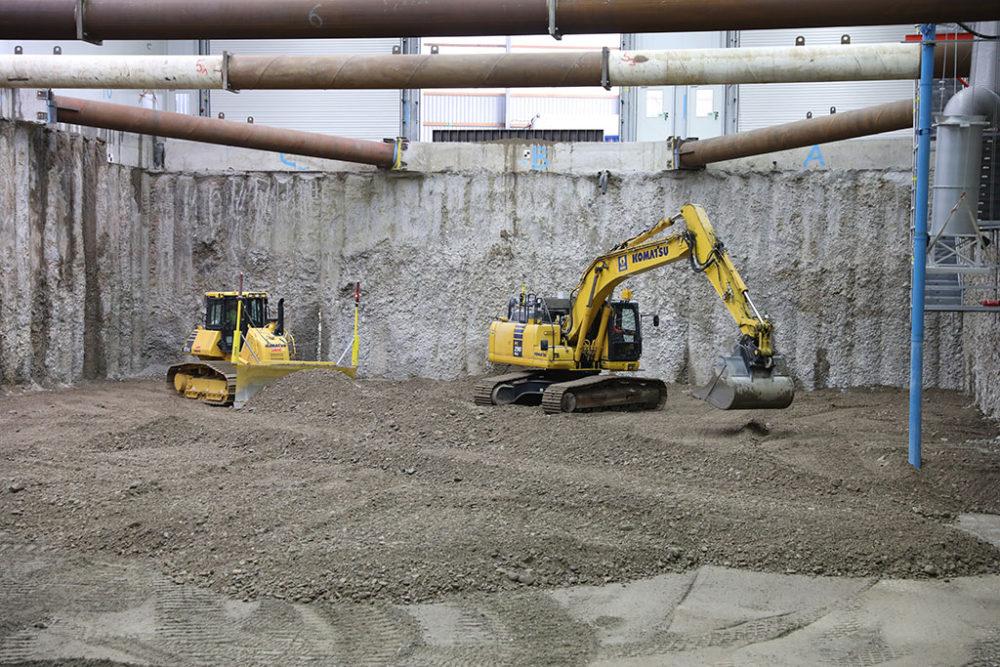 Schwere Baumaschinen übernehmen die Verteilung des eingebrachten Materials. Quelle: Pressefoto Roche.